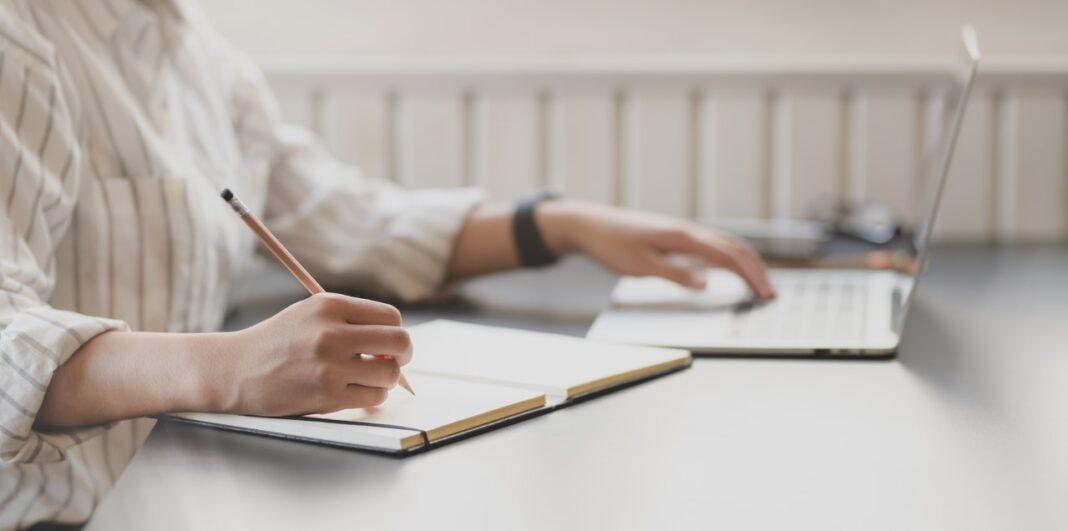 Person skriver i notesblok imens hun er på computeren